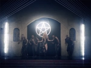 This snapshot from the music video 'Die Young' by pop singer Kesha is a good example of how symbols of light are demonized. The symbol of an upright pentagram hangs in an old church where Kesha engages in orgiastic acts.