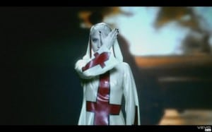 Pop star covered in upside down crucifixes and doing a symbolic gesture in covering their eye – creating the all-seeing eye.