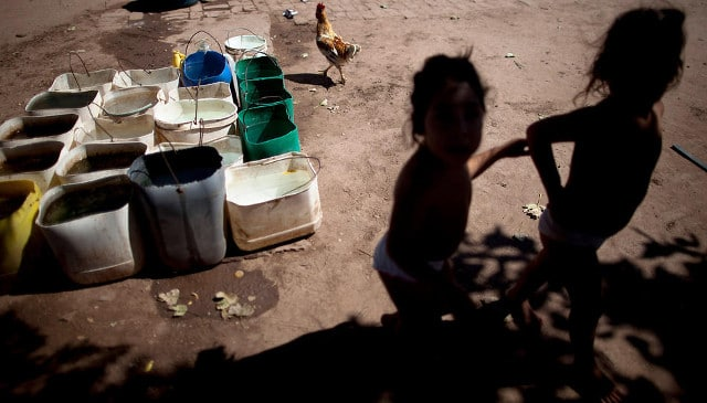 Erika, left, and her twin sister Macarena, who suffer from chronic respiratory illness, play in their backyard near recycled agrochemical containers filled with water that is used for flushing their toilet, feeding their chickens and washing their clothes, near the town of Avia Terai, in Chaco province, Argentina, on March 31, 2013. CREDIT: Natacha Pisarenko/AP
