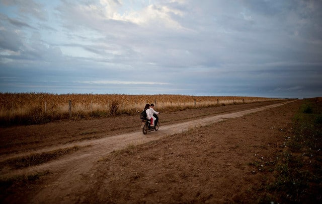 Students ride a motorbike past a field of biotech corn on their way to school in Pozo del Toba, Santiago del Estero province, Argentina, May 3, 2013. CREDIT: Natacha Pisarenko/AP