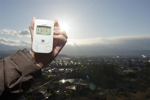 A Greenpeace team member holding a Geiger counter displaying radiation levels of 5.78 microsievert per hour outside Fukushima city on March 27, 2011. Radiation levels far exceed exposure limits considered �safe� for the 400,000 strong human population below.